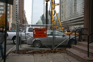 "Cars are parked on the construction site behind a fence and this ""Sidewalk Closed"" sign on Arch Street between 19th and 20th, forcing pedestrians to cross mid-block."