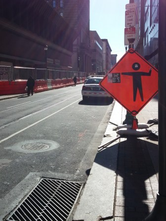 1100 Market -11th St. peds in traffic, sign with tripping hazard legs